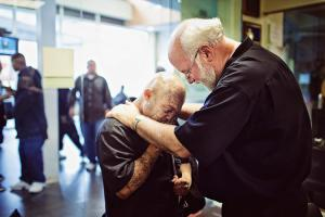 Father Gregory prays with a client.